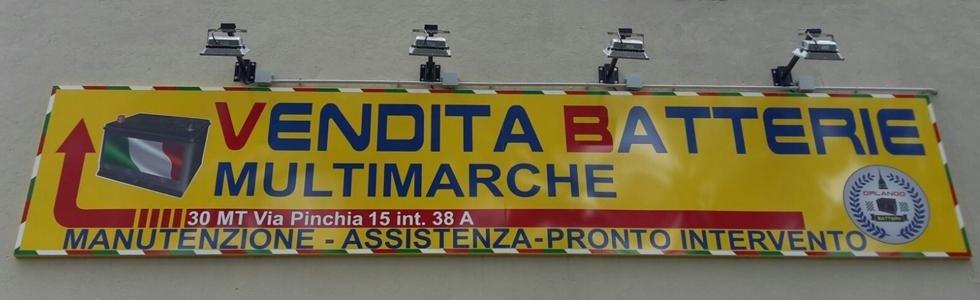 insegna pubblicitaria con scritta:  VENDITA BATTERIE MULTIMARCHE 30 mt via Pinchia 15 int. 38 A MANUTENZIONE ASSISTENZA PRONTO INTERVENTO