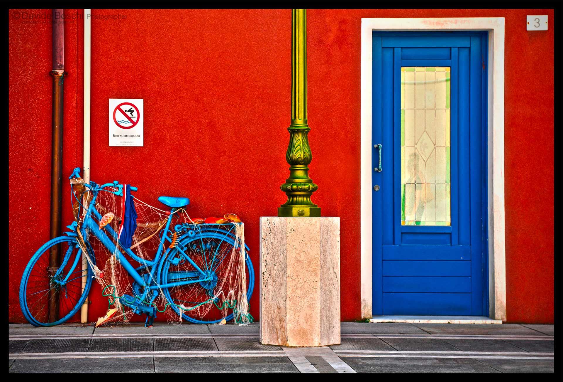 Foto di una bicicletta, avvolta in una rete,un cartello di vietato saltare in acqua nella parete