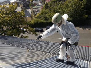Roof restoration repairs man spraying painting roof heritage and slate roofing hobart australia