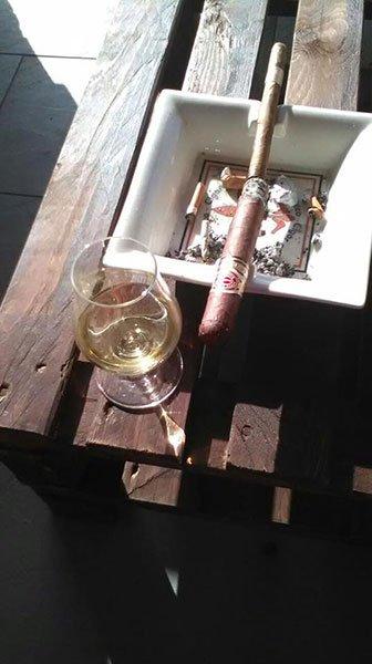 un tavolino con un bicchiere di vino e un sigaro acceso