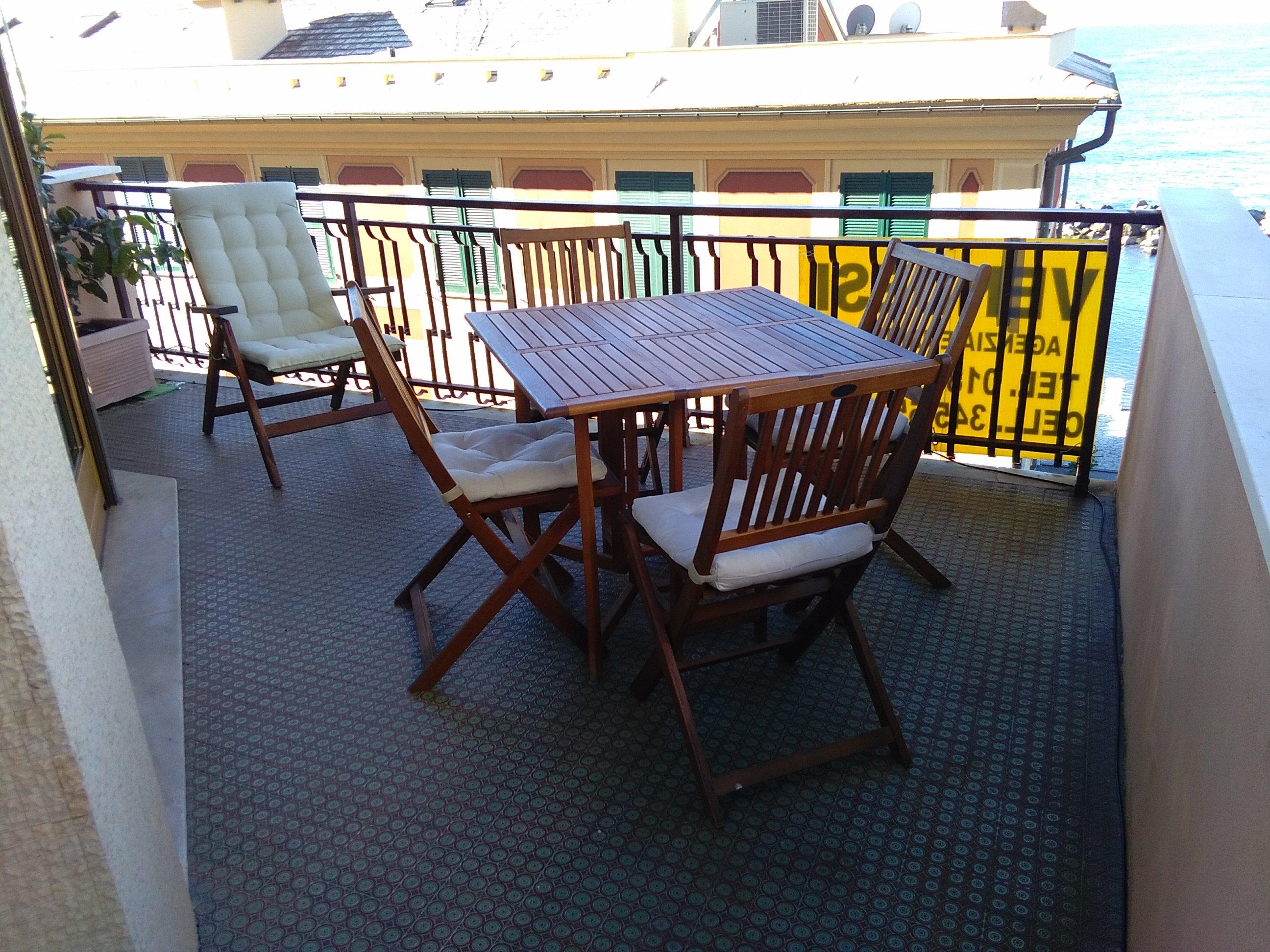 un tavolo di legno con delle sedie su un balcone