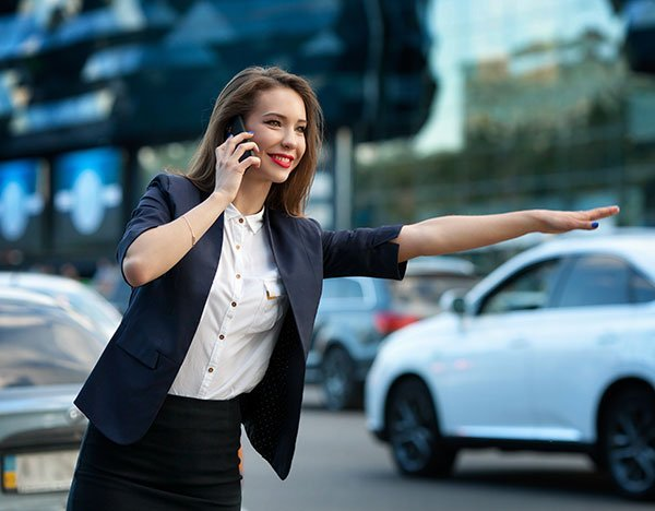 businesswoman talking on the phone catches a taxi