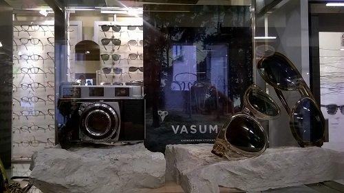 una macchina fotografica e due paia di occhiali da sole appoggiati su delle pietre