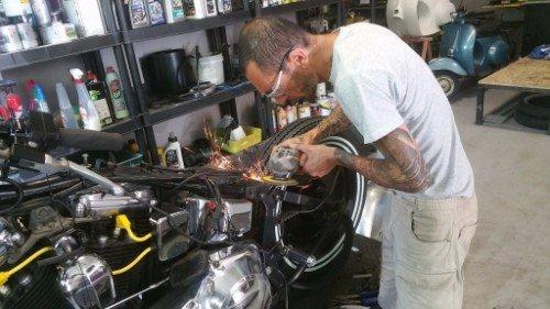 Uomo che ripara in una moto, perfezionando un pezzo del motore