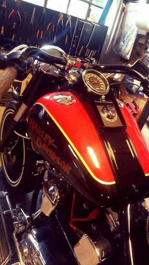 Serbatoio di Harley Davidson di colori nero e rosso con profilo giallo e manubrio customizzato