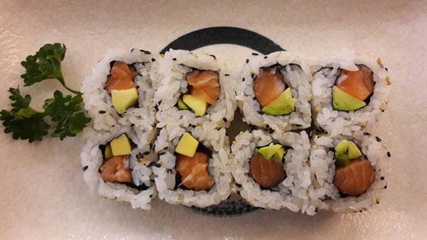 Un piatto di sushi con avocado e salmone appoggiato su uno sfondo bianco e foglie di prezzemolo sulla sinistra