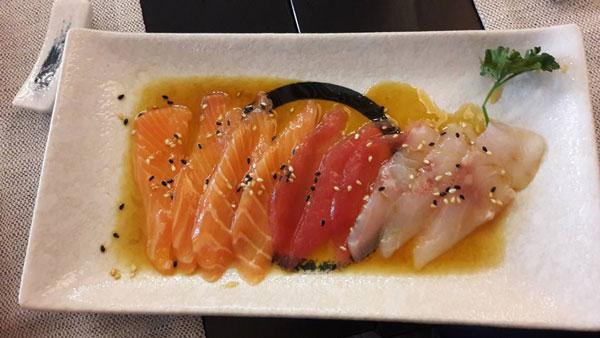 Filetti di salmone, tonno e pesce spada serviti nel piatto quadrato con della salsa, pochi semi di sesamo e foglia di prezzemolo