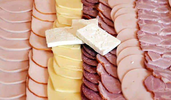 salumi di diverso genere tagliati a fette rotonde in fila gli uni accanto agli altri con anche alcuni formaggi