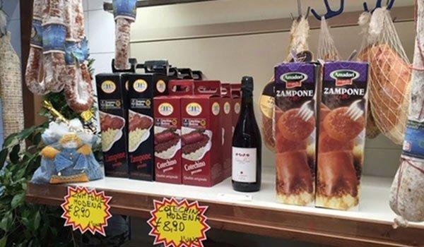 cestini con zampone, cotechino,bottiglie di vino e sopra salumi appesi