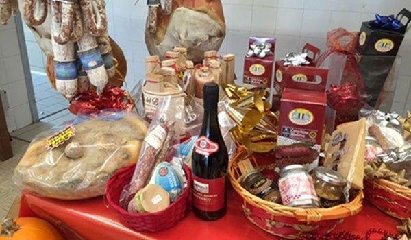 salumi appesi, confezioni di zampone e cotechino e una bottiglia di vino
