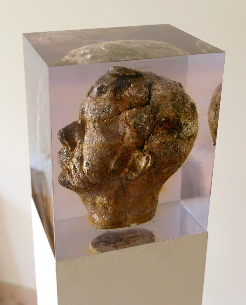 Joseph II 2012-2014, Inclusion of the bread head 21x25x28 cm op een sokkel van 85 cm hoog en 21x25x28 cm Bread head, moulds, polyester € 4.900      Het beeld van Joseph is gemaakt van brood, gegoten in epoxy. De kunstenaar Giuseppe Licari heeft een zelfportret gemaakt. Giuseppe betekent Joseph. Hij heeft een mal van zijn hoofd gemaakt en in die mal een brood gebakken. Dit broodhoofd heeft een paar maanden in zijn atelier gestaan. Van het proces van schimmelen zijn foto's gemaakt. Na een paar maanden is het hoofd van brood ingegoten in epoxy. Door de chemische reactie van het schimmel met epoxy ontstond de zilverkleur.  Het beeld is geïnspireerd over de viering van de naamdag van St. Joseph in Sicilië. Joseph is de onbaatzuchtige vader, die weggeeft, zonder iets te willen ontvangen. Op deze feestdag bakken de moeders en vrouwen in Sicilië veel kleine broodjes, die worden naar de kerk gebracht. In de avond worden de broodjes uitgedeeld.