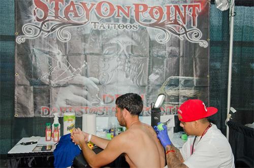 Customer getting a back tattoo at Flight 914 event