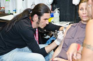 Tattoo artist working on the customer at the Flight 913 event