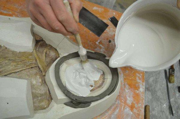 un uomo sta dipingendo con un pennello un oggetto in ceramica posto su un piano da lavoro