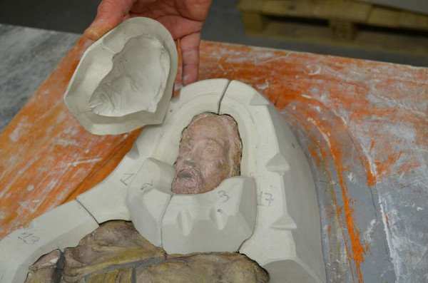 un uomo sta applicando uno strato in ceramica di uno stampo parzialmente finito raffigurante un uomo