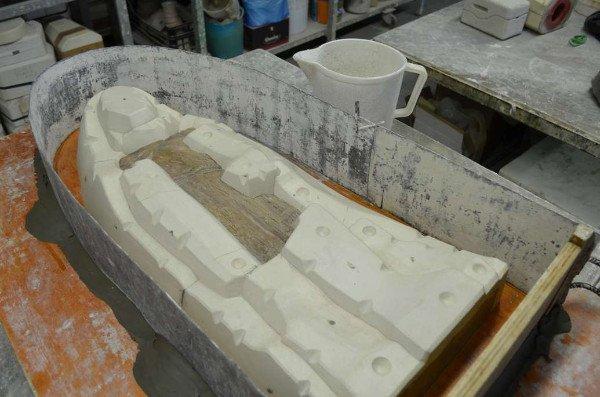 vista di un contenitore in metallo con all'interno uno stampo in ceramica e affianco una brocca in plastica