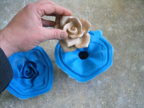 un fiore in ceramica color beige e due stampi a forma di fiori blu