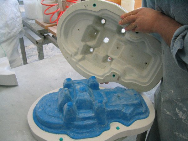 un uomo sta mettendo uno stampo in ceramica sopra ad un altro di color blu