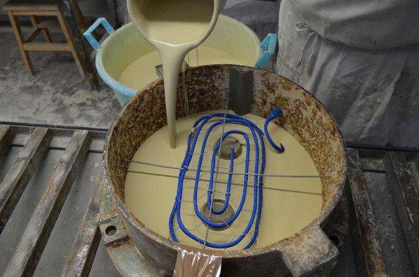 una persona con una brocca di plastica sta versando della ceramica liquida in un secchio di metallo