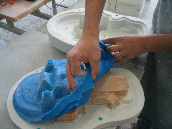 due mani stanno mettendo uno stampo in ceramica blu sopra ad un altro
