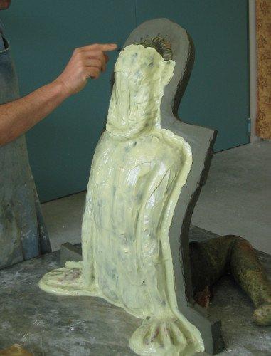 una mano indica uno stampo in ceramica raffigurante una figura umana