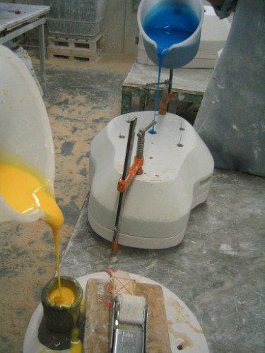 una brocca di plastica con del liquido blu colante su un macchinario di plastica bianco e dall'altra parte un secchio di plastica bianco che versa del liquido giallo in un contenitore nero in ceramica