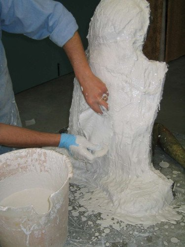 due mani stanno applicando della ceramica liquida su una scultura