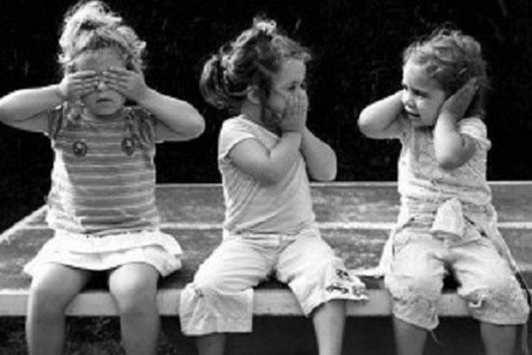 una foto in bianco e nero di tre bambine che mimano i gesti di non vedo,non sento e non parlo