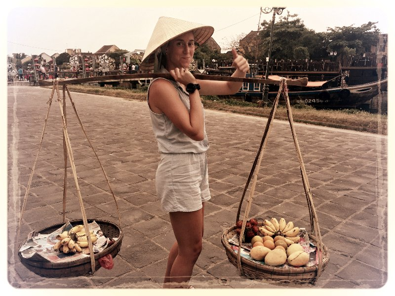 Young American woman carrying fruit on her shoulders in Vietnam