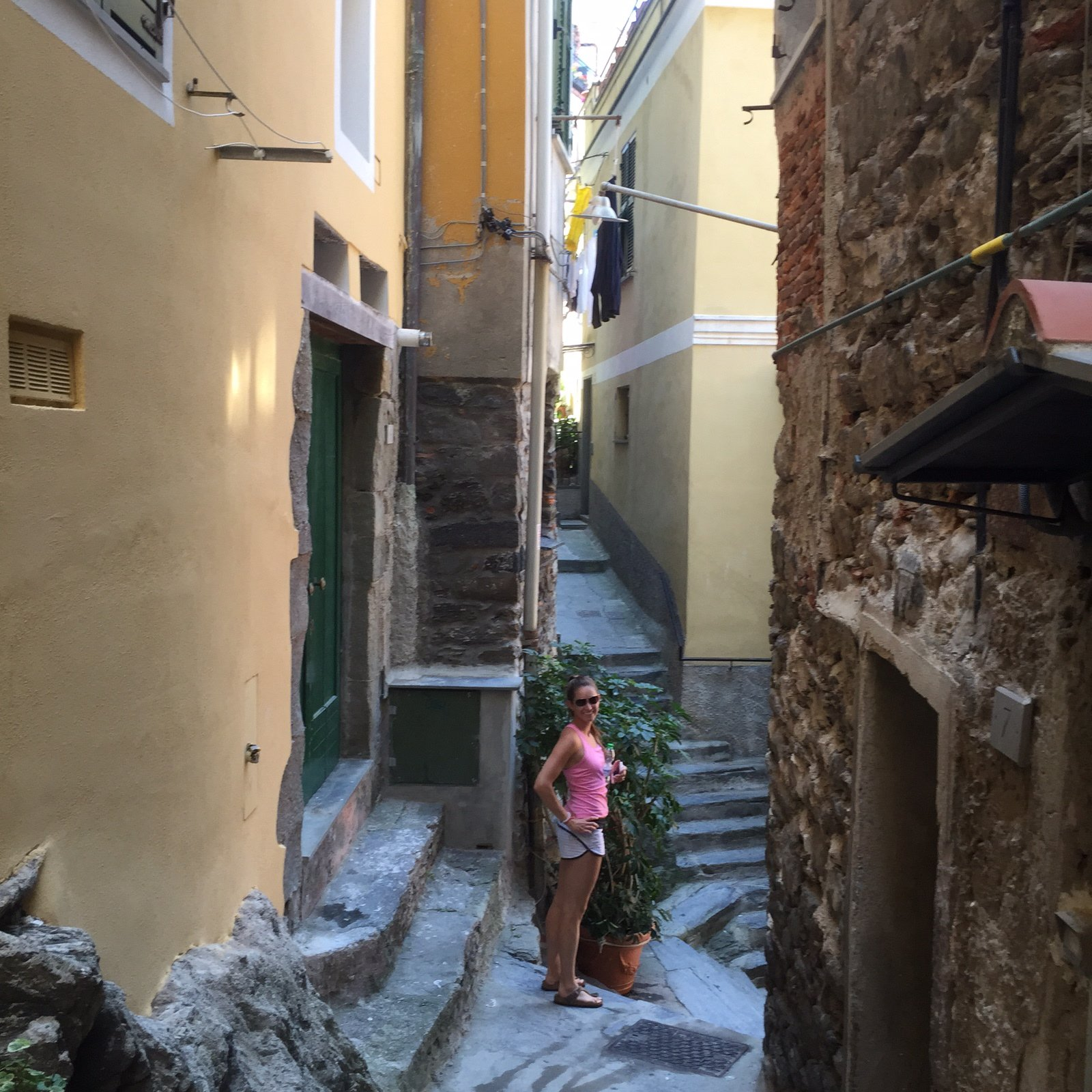 Young American woman walking down narrow and steep walkways in Italy