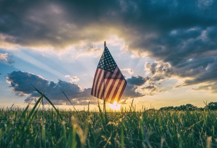 American flag in a green field with clouds and sunset overhead