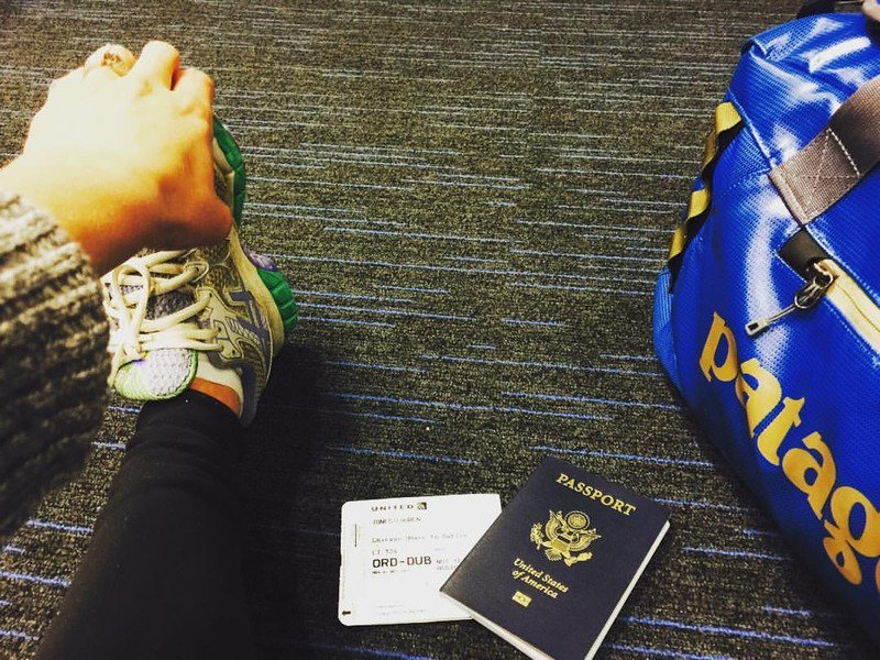 Image of woman stretching her legs in airport with passport and luggage next to her.