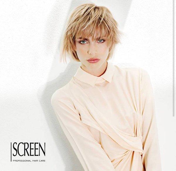 modella con camicia maniche lunghe e taglio biondo corto in posa per SCREEN