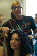 parrucchiera durante una piega con piastra per capelli a una cliente