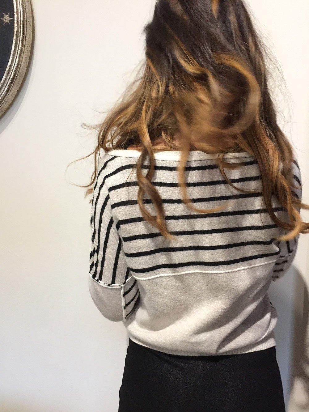 una ragazza con un maglione grigio a righe nere vista dal dietro