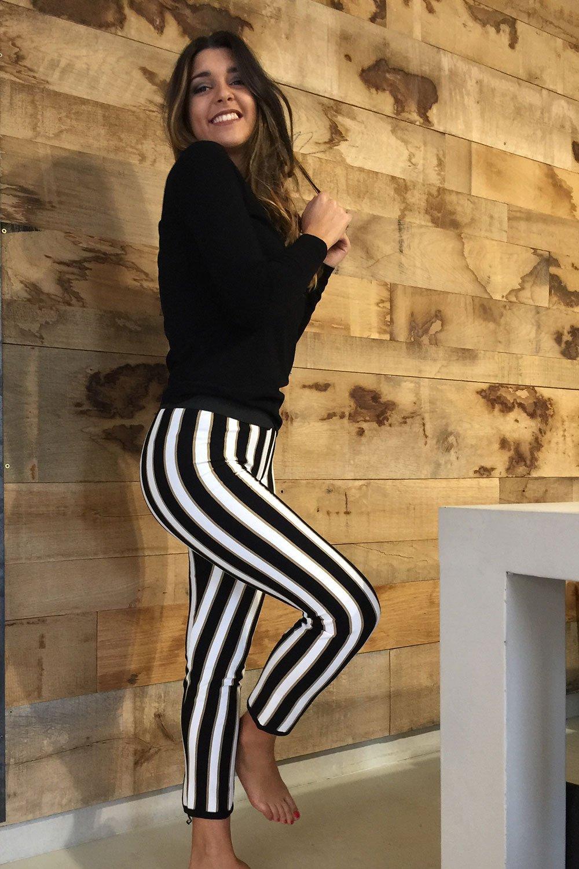 una ragazza con un maglione nero e dei pantaloni bianchi a righe nere