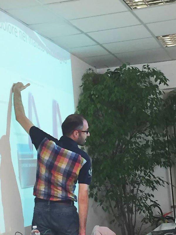 un uomo girato di spalle con una maglietta nera a quadretti di diversi colori mentre indica una parete di un muro su cui è proiettata una presentazione