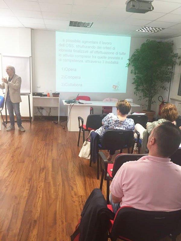 un'aula con dentro delle persone sedute,una persona in piedi che spiega e una presentazione proiettata a muro
