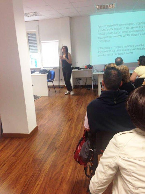 una donna in piedi che spiega, delle persone sedute su delle sedie all'interno di una classe e una presentazione proiettata sul muro