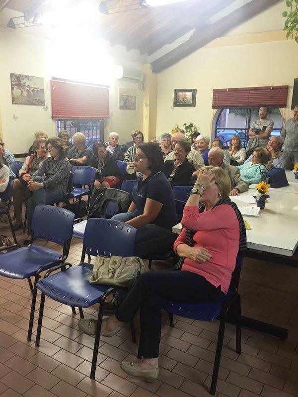 delle signore, alcune anziane e altre di mezza età sedute su delle sedie blu