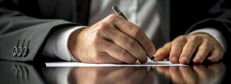 A close up of a man signing a document