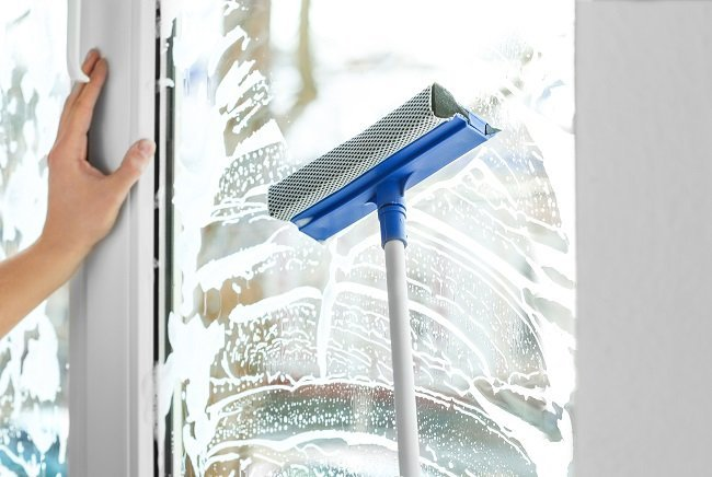 Donna pulisce una vetrata