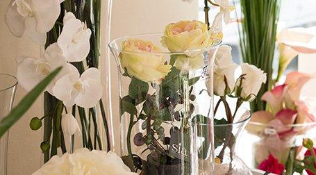 Dei vasi con delle rose e orchidee di color bianco