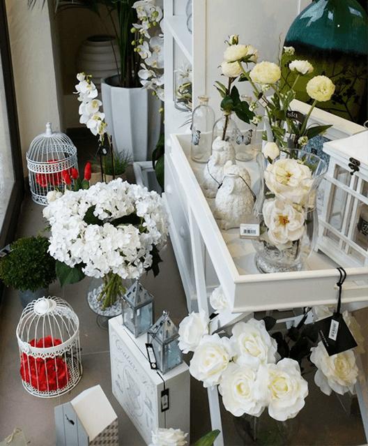 uno stand con dei vasi di fiori bianchi e delle lanterne