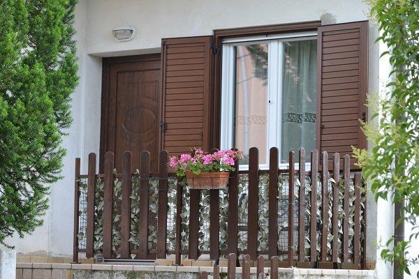 una finestra aperta con delle persiane in legno