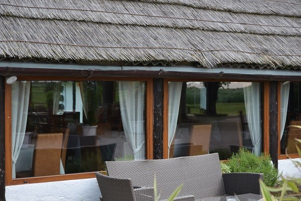 delle finestre in legno con vista dei tavoli  di un ristorante