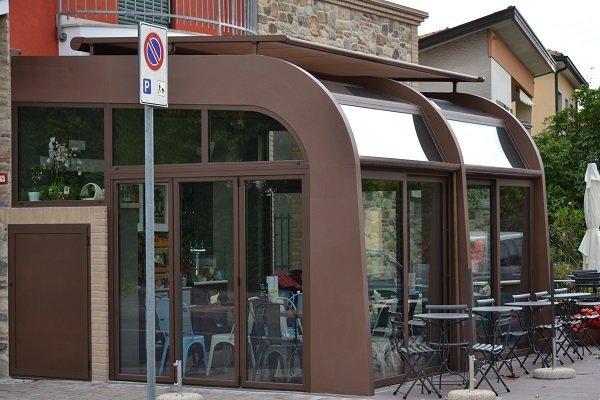 una struttura moderna di color marrone con delle vetrate e dei tavoli all'interno