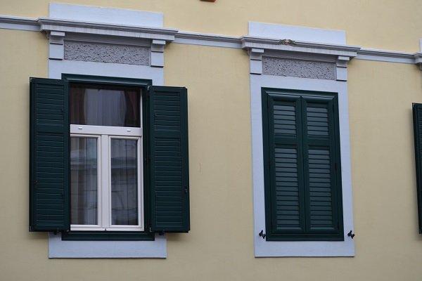 un edificio con vista delle finestre con delle persiane di color verde