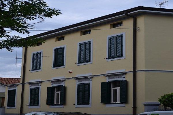 un edificio giallo con vista delle finestre con delle persiane di color verde