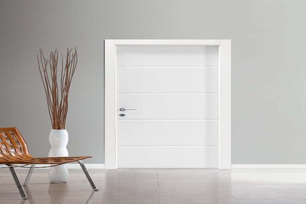 una porta di color bianco e accanto un vaso